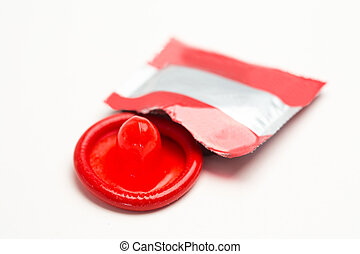 Red condom with wrapper on white background