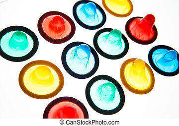 Twelve brightly colored condoms on white background
