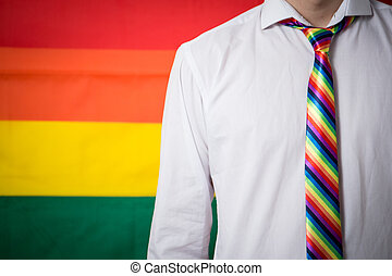 Man wearing shirt and rainbow tie on rainbow flag background