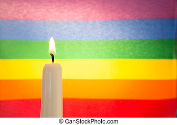 Candle against rainbow flag for gay pride