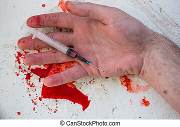 Lifeless hand holding bloody syringe in pool of blood