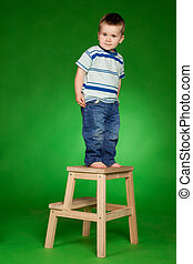 little boy standing on stairs in studio