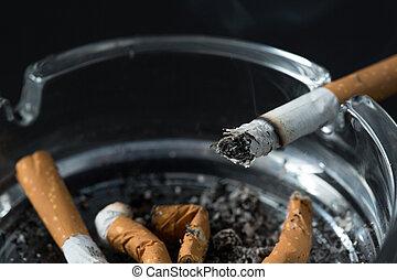 Burning cigarette butt in ashtray