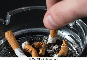 Hand putting out a cigarette in ashtray on black background