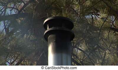Smoking chimney on roof with pine trees