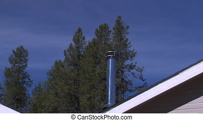 clean burning chimney with heat waves and pine tree