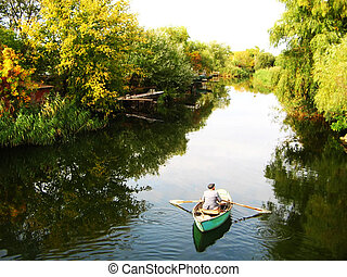 Beautiful landscape - The old man on the boat on a river...