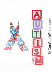 Autism awareness ribbon beside stacked blocks spelling...