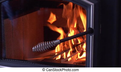 hand closes glass door on wood stove with fire