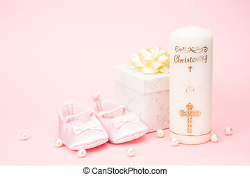 Christening candle with pink baby booties and gift box on...