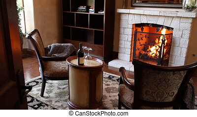cozy chairs in front of fireplace with bottle of wine