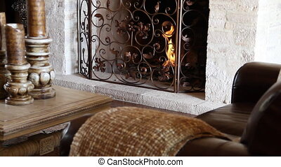 leather chair in front of fireplace and ornate metal work