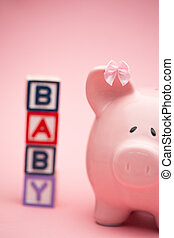 Piggy bank and blocks spelling baby on pink background