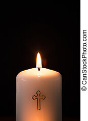 Catholic candle burning on black background