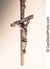 Close up of silver crucifix hanging from rosary beads