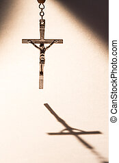 Cross casting a shadow - Cross hanging from rosary beads...