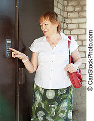 Mature woman uses intercom in steel door