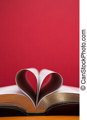 Embossed pages of book folded to make heart on red...