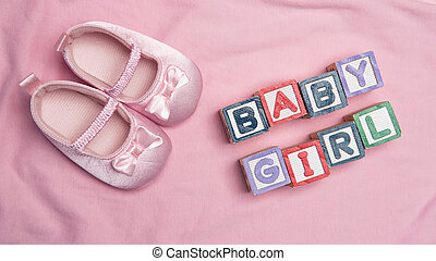 Baby girl spelled out in blocks with pink booties on pink...