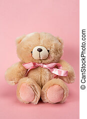 Teddy bear with pink ribbon on pink background