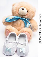 Teddy bear with blue ribbon and white booties on white...