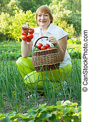 mature woman in vegetables garden - Happy mature woman in...