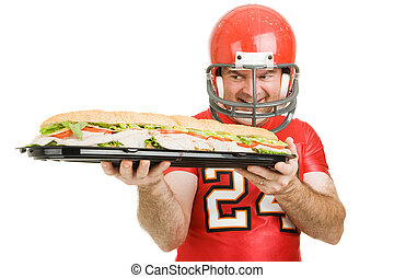 Man Sized Hunger - Football player hungrily looking at a...