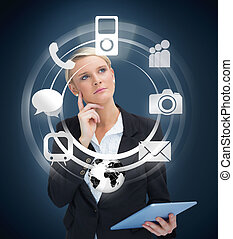 Thoughtful businesswoman with tablet pc considering various...