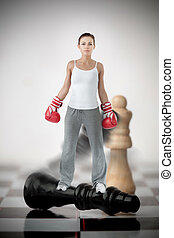 Female boxer standing on black chess piece on chessboard