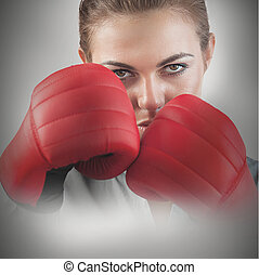 Powerful female boxer with fists up and red boxing gloves