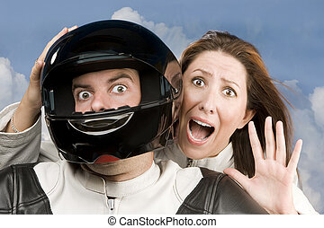 Man and fearful woman on a motorcycle in studio