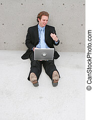 businessman sitting outside with his wireless laptop sitting...