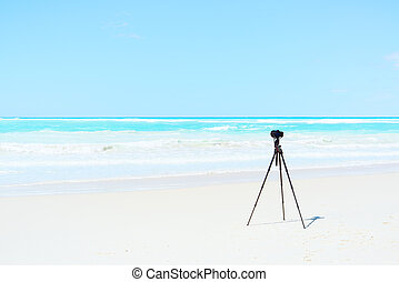 Digital Camera, tripod and filters on white beach ready for...