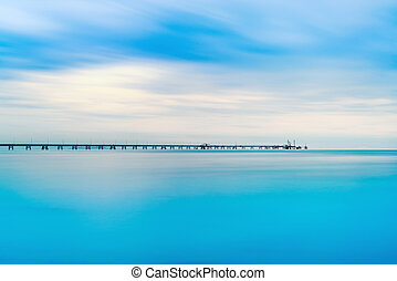 Industrial pier on the sea. Long exposure photography.