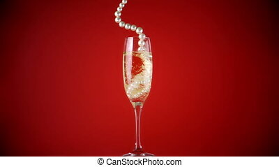 String of pearls falling into champagne flute in slow motion