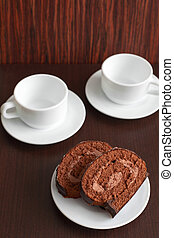 chocolate cake on a plate with a cup