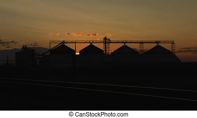 time lapse silhouette of grain elevators
