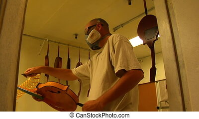 worker wearing a respirator sprays finish on mandolin