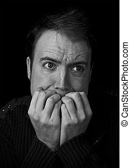 fear, man scared biting fingernails black and white portrait