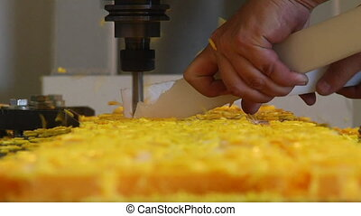 man holds guards as industrial milling machine carves...