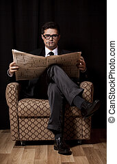 Man with cigarette and newspaper sitting in vintage armchair