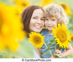 Happy family with beautiful sunflowers in spring field