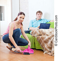 couple at home - Clean up woman, while her husband lying on...