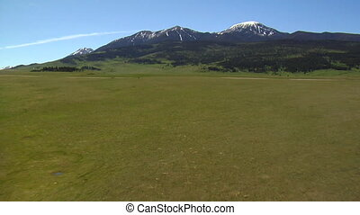 Aerial shot of grassy meadow near mountains