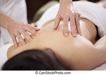 Getting a back massage at a spa - Closeup of a young woman...