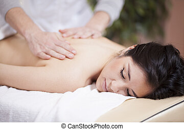 Back massage at a spa - Cute young woman getting a back...