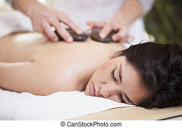 Hot stone massage at home - Pretty woman getting a hot stone...