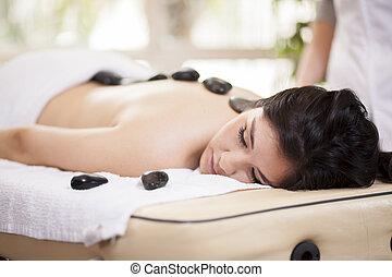 Hot stone massage at a spa - Beautiful woman enjoying a hot...
