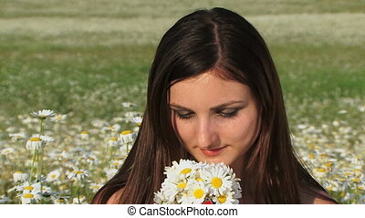 Smelling daisies - Beautiful woman smelling a bouquet of...