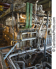 Giant pipes, tubes and equipment inside modern industrial power plant, night scene